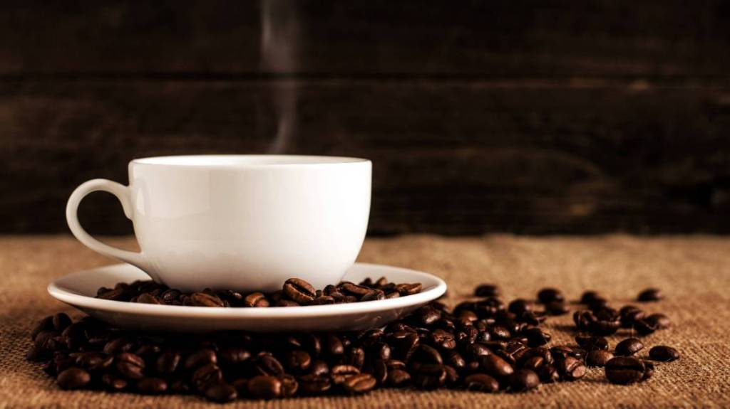 coffee cup sitting on coffee beans