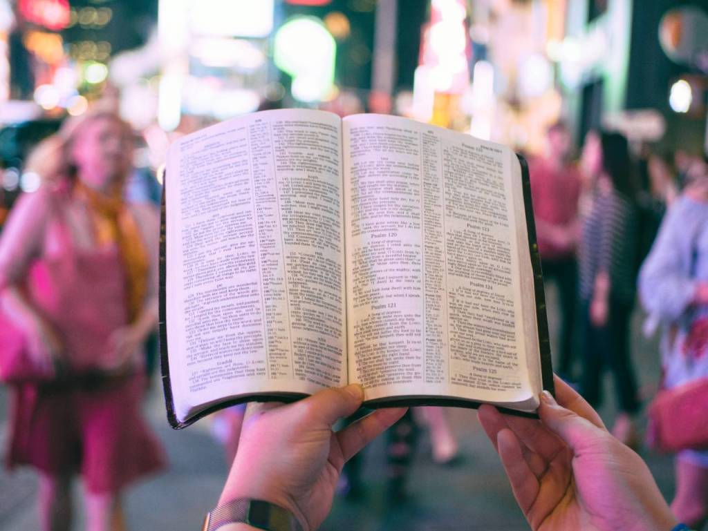a man holding an open Bible in a crowd