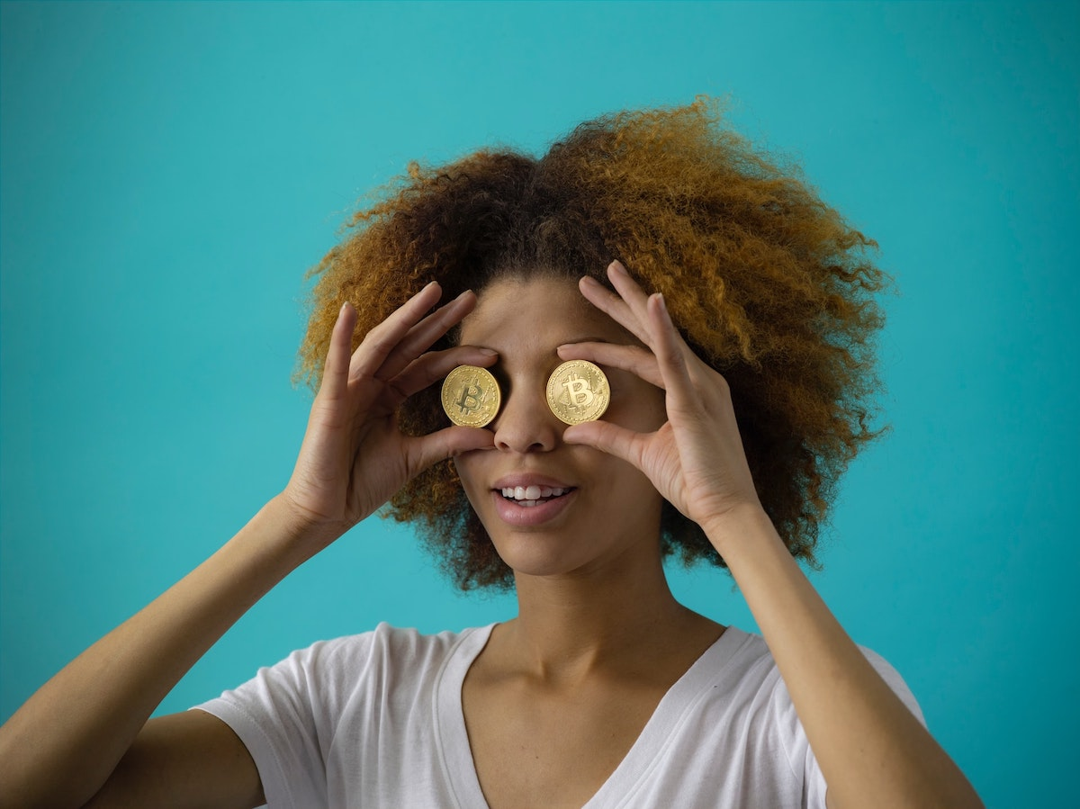 woman holding two round gold coins